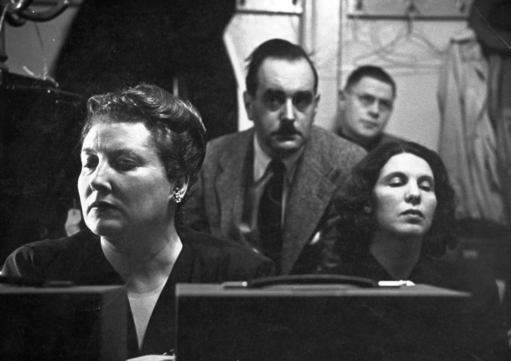 Eyes closed and their faces mask-like in deep reverie, Helen Traubel (left) and Herta Glaz (right) sit in recording booth with sound engineers listening to their duet from Tristan.