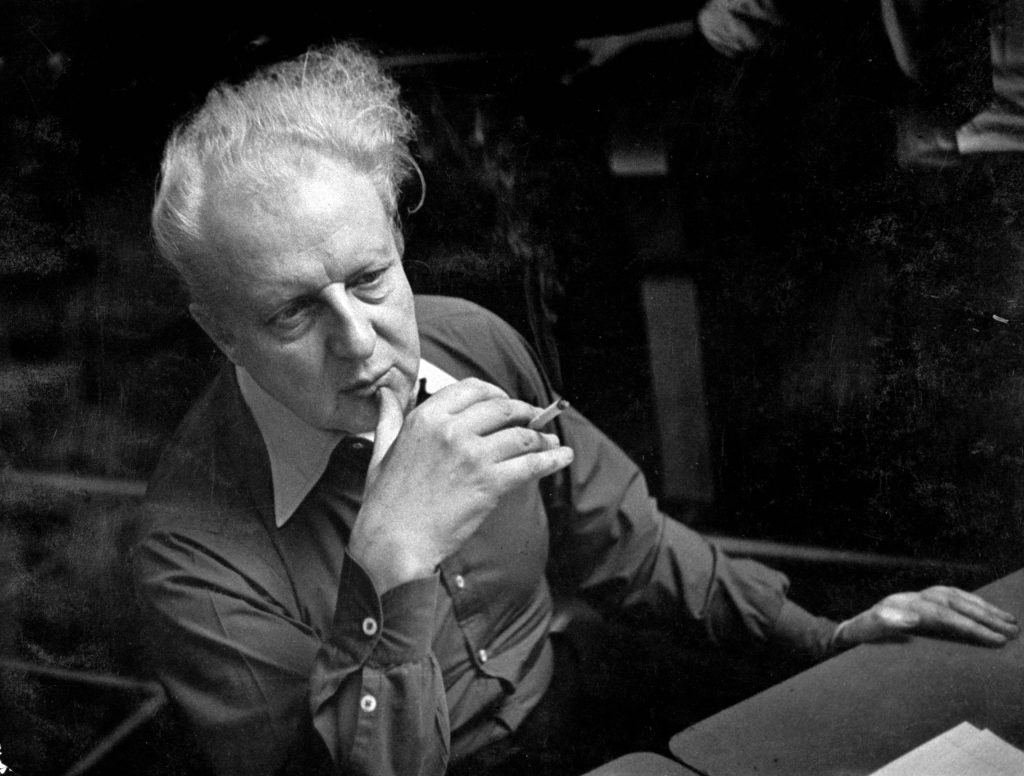 Leopold Stokowsky smokes a cigarette and listens during a recording session.