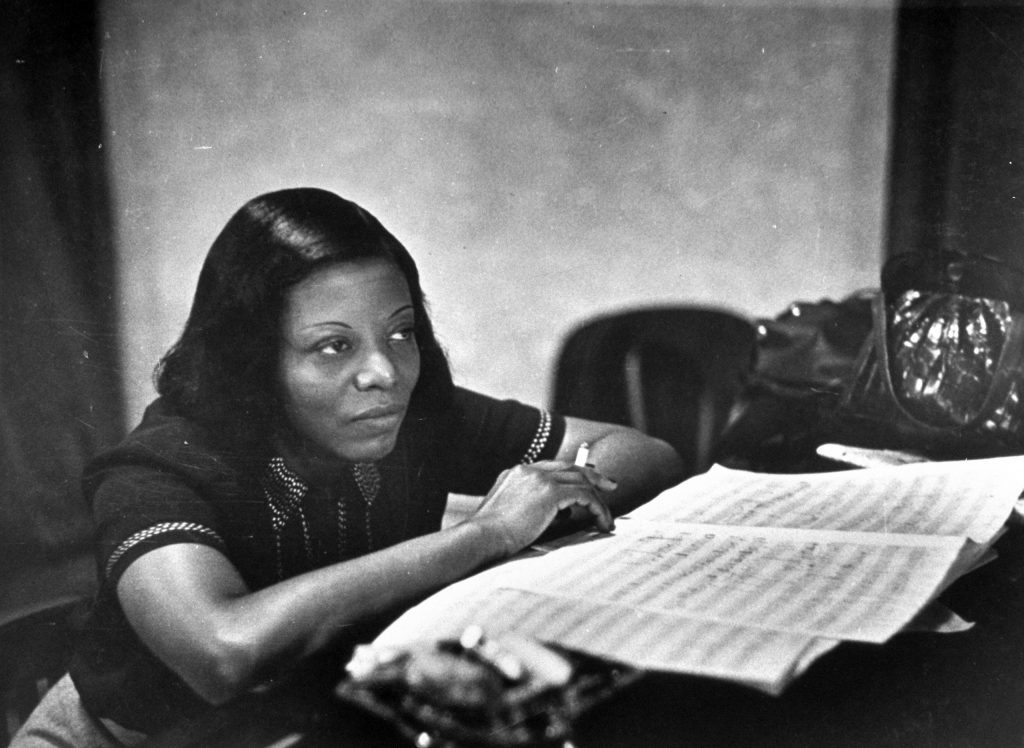 Jazz musician Mary Lou Williams, music in front of her, listening to playback of recording she has just made.