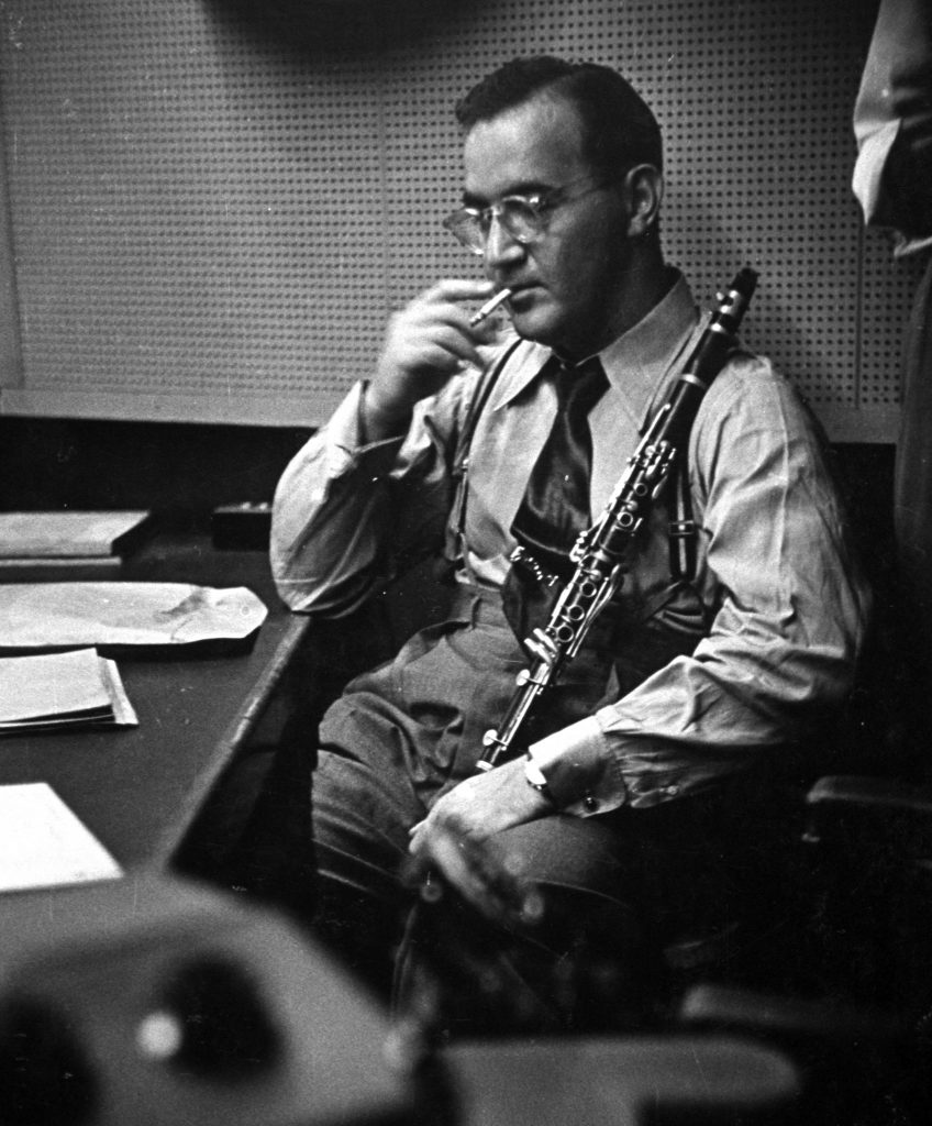 Clarinetist Benny Goodman smokes a cigarette while listening in a CBS recording session.