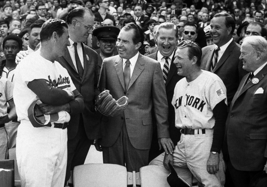 President Richard Nixon throws out the first pitch as manager Ted Williams of the Washington Senators, the MLB Commisioner Bowie Kuhn and manager Ralph Houk of the New York Yankees look on before opening day on April 7, 1969 at RFK Stadium in Washington, D.C.