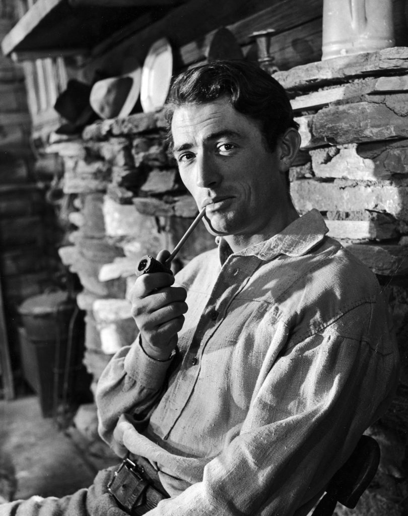 """Gregory Peck smoking a pipe for a scene in the movie """"The Yearling."""" 1947."""