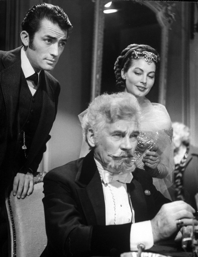 """Gregory Peck and Ava Gardner watching Walter Huston as he gambles in scene from film """"The Great Sinner."""" 1949."""