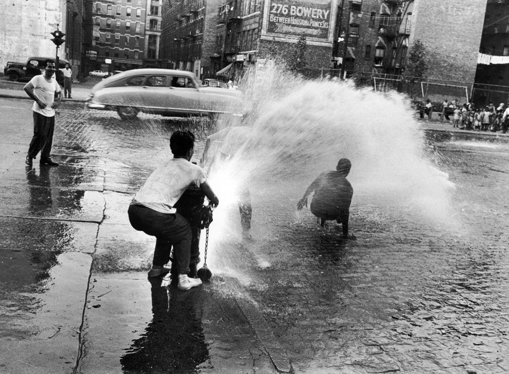 Children playing in water during a heat wave in New York City, 1953.