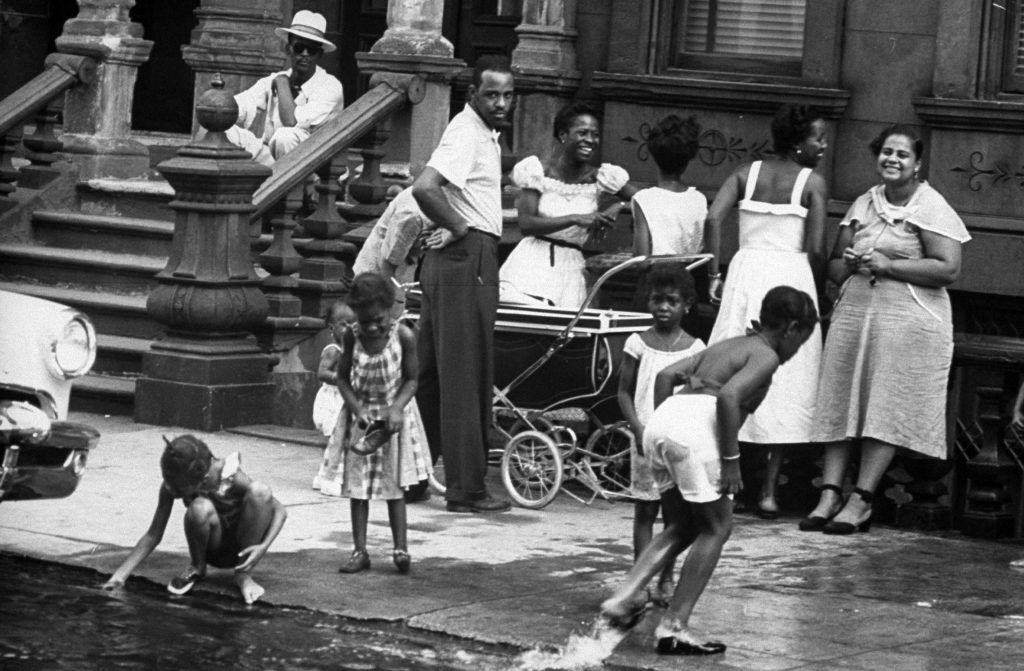 People spending time outdoors during an ongoing heatwave during the summer of 1953 in New York City.