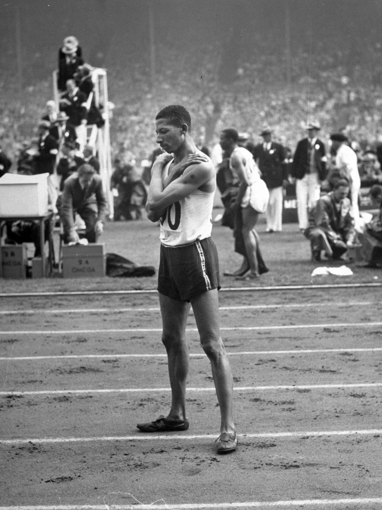 Jamaican athlete Herb McKenley standing on a track at the 1948 summer Olympics in London.