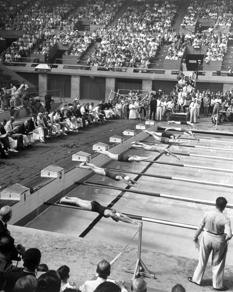 Competitors diving into pool during swimming events at the 1948 summer Olympics in London.