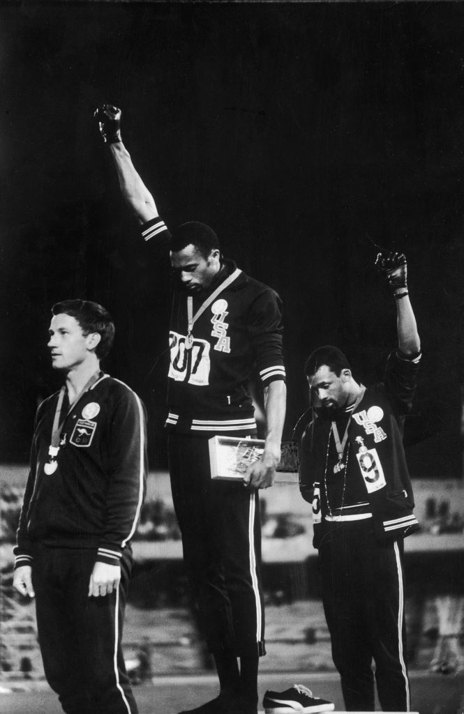 American track stars Tommie Smith (C) and John Carlos (R) standing on podium after winning gold and bronze Olympic medals, respectively, raising black-gloved fists, in support of civil rights/black power, while Australian silver medalist Peter Norman stands by at the 1968 summer Olympics in Mexico City, Mexico.