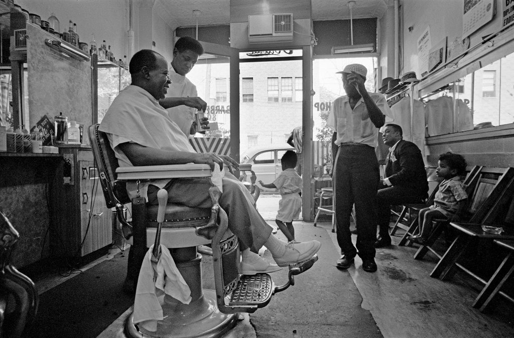 Louis Armstrong at his neighborhood barbershop in Queens, Louis Armstrong gets a beer and a haircut. New York City, 1965.