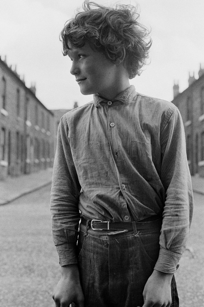 The boy turns his head as he hears his mother's call from down the street. Manchester, England, 1968.