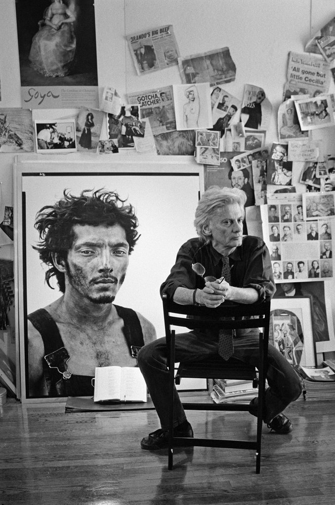 Richard Avedon sits in his studio before a wall of miscellaneous clippings and his portrait of oil field worker Roberto Lopez. New York City, 1994.
