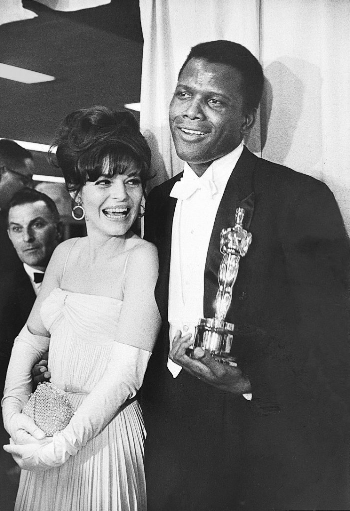 Anne Bancroft backstage at the Academy Awards with Sidney Poitier who holds his Oscar statuette for Best Actor in a Leading Role, given for his performance in the film 'Lilies of the Field,' 1964.