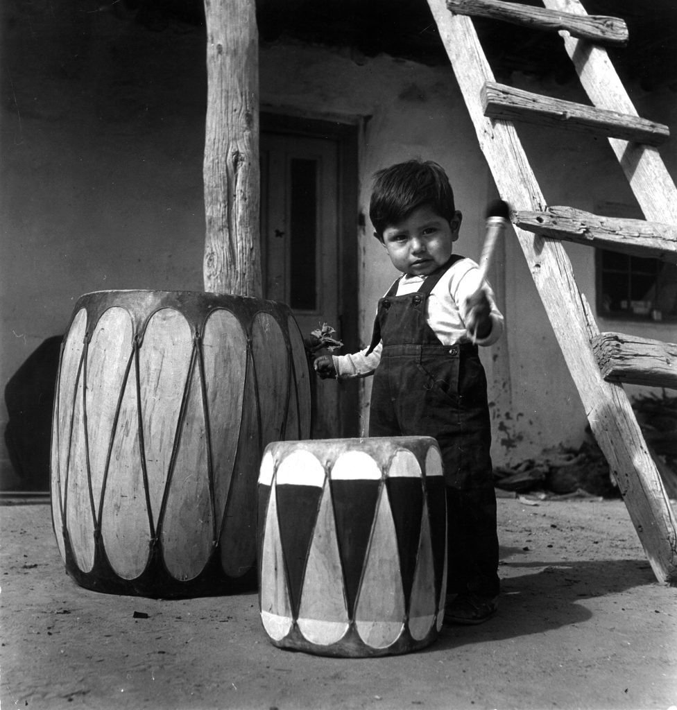 Native American boy of the Chochiti tribe playing drum outside his home, Sante Fe, New Mexico in 1947.