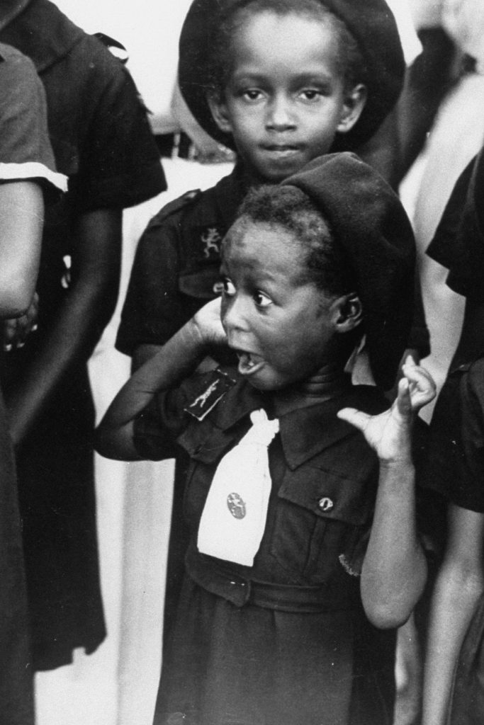 A Jamaican girl scout with surprised look as she watches the arrival of Queen Elizabeth II. Jamaica, 1953.