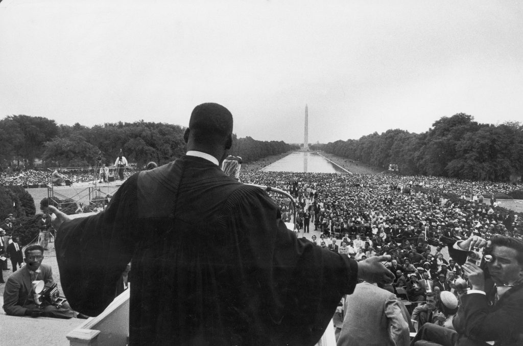 "Dr. Martin Luther King Jr. speaks in front of the Lincoln Memorial before 25,000 people at the Prayer Pilgrimage for Freedom, May 1957 to mark the third anniversary of the landmark supreme court decision, Brown v. the Board of Education, which outlawed segregation in public schools. Among his landmark early addresses, King's speech that day was known as ""Give Us the Ballot."""
