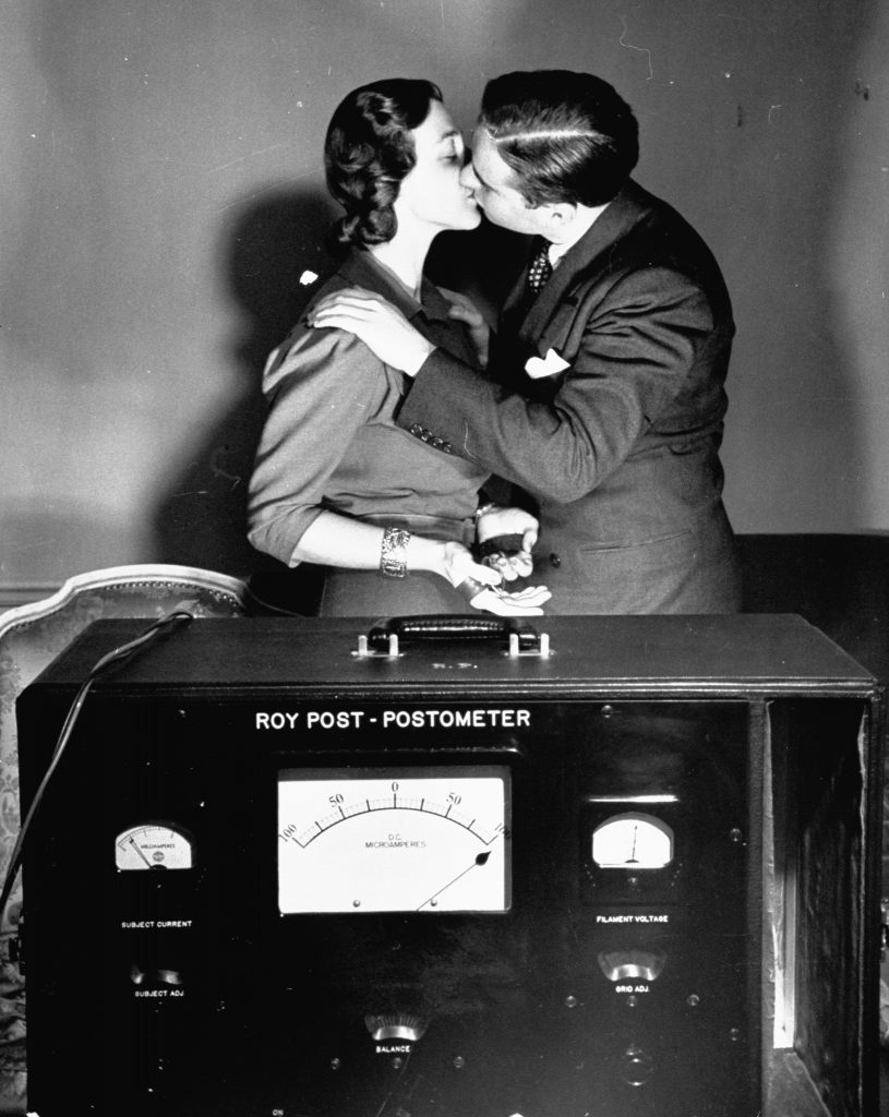 A man and woman kissing while geared to a lie detector machine to measure the emotional reaction,1939.