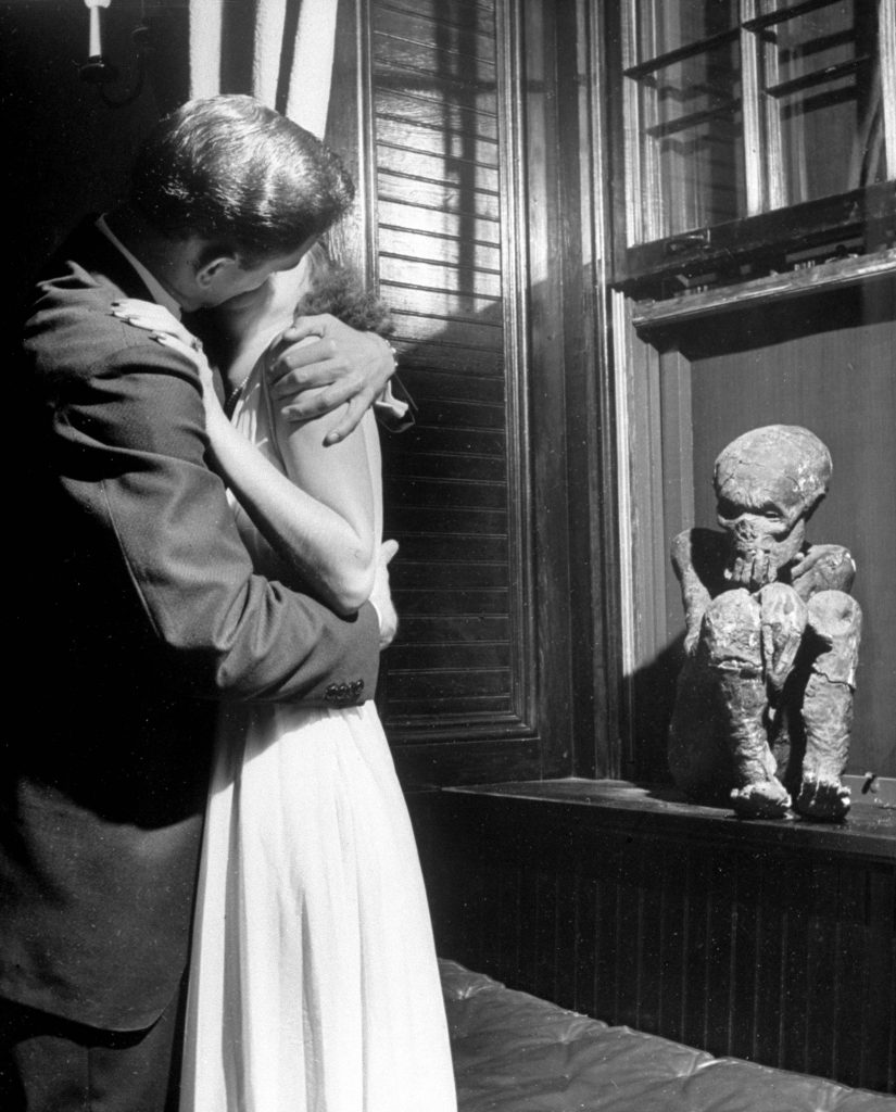 "Couple kissing in front of the Delta Tau Delta mummy at the University of the South. Girls are told: ""Kiss mummy or kiss me."" 1940."