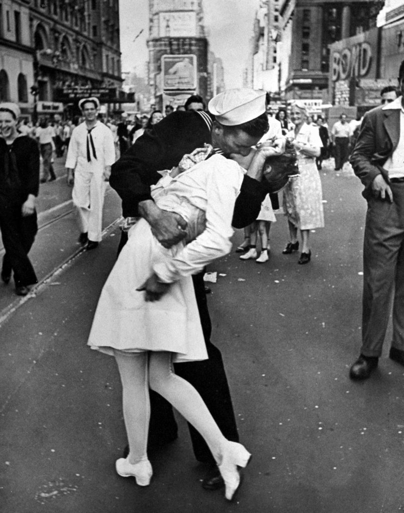 A jubilant American sailor clutched a dental assistant in a back-bending kiss at a moment of spontaneous joy about the long awaited WWII victory over Japan. Taken on V-J Day, 1945, as thousands jammed Times Square. In recent decades this iconic photograph has engendered condemnation, after Greta Zimmer Friedman, the woman being kissed by the sailor (believed to have been George Mendonsa) said that the kiss was nonconsensual. In 2019, shortly after Mendonsa died at age 95, a statue of the kiss in Florida was tagged with #metoo graffiti.