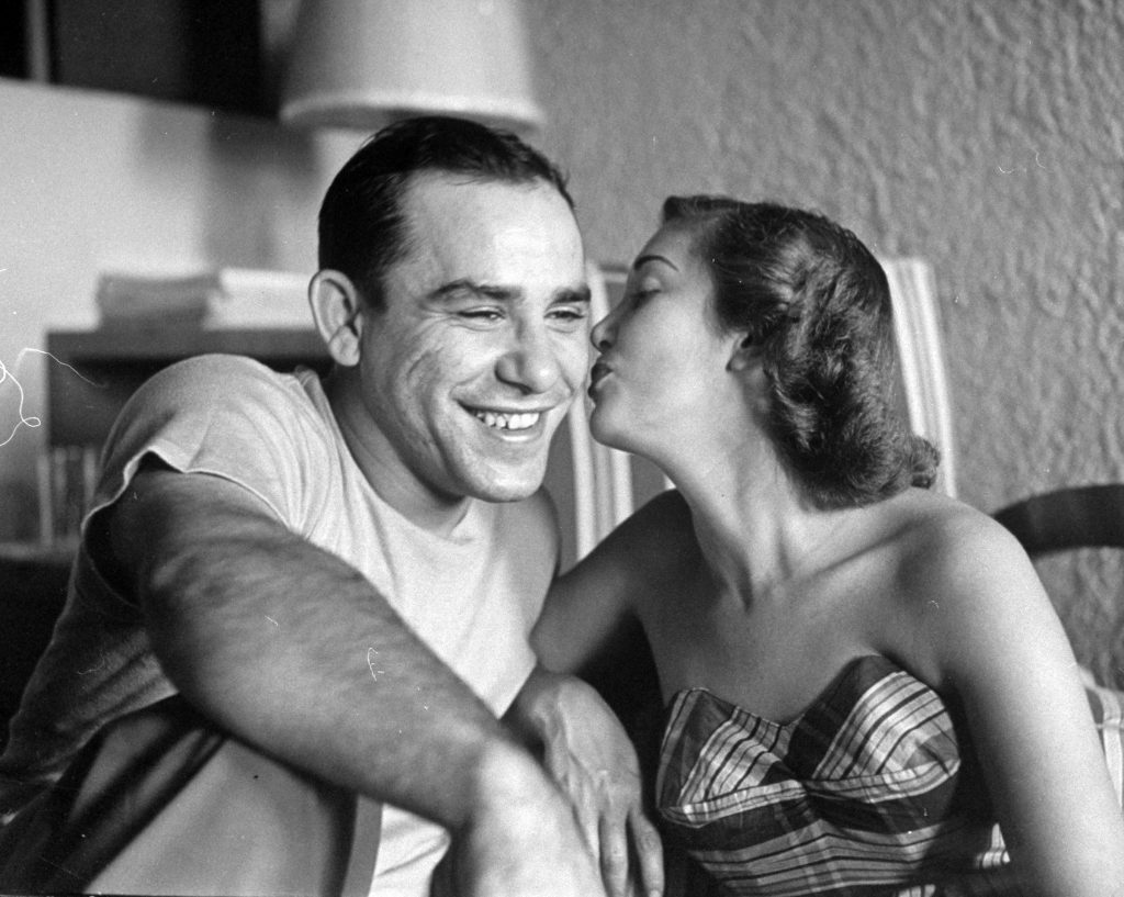 Baseball player Yogi Berra getting kiss from his wife, Carmen, before he leaves for clubhouse. 1949.