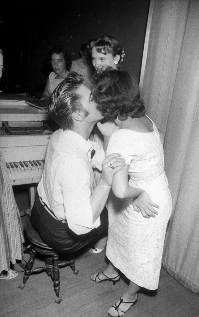 Elvis Presley tenderly kissing the cheek of a female admirer backstage before his concert, 1956.
