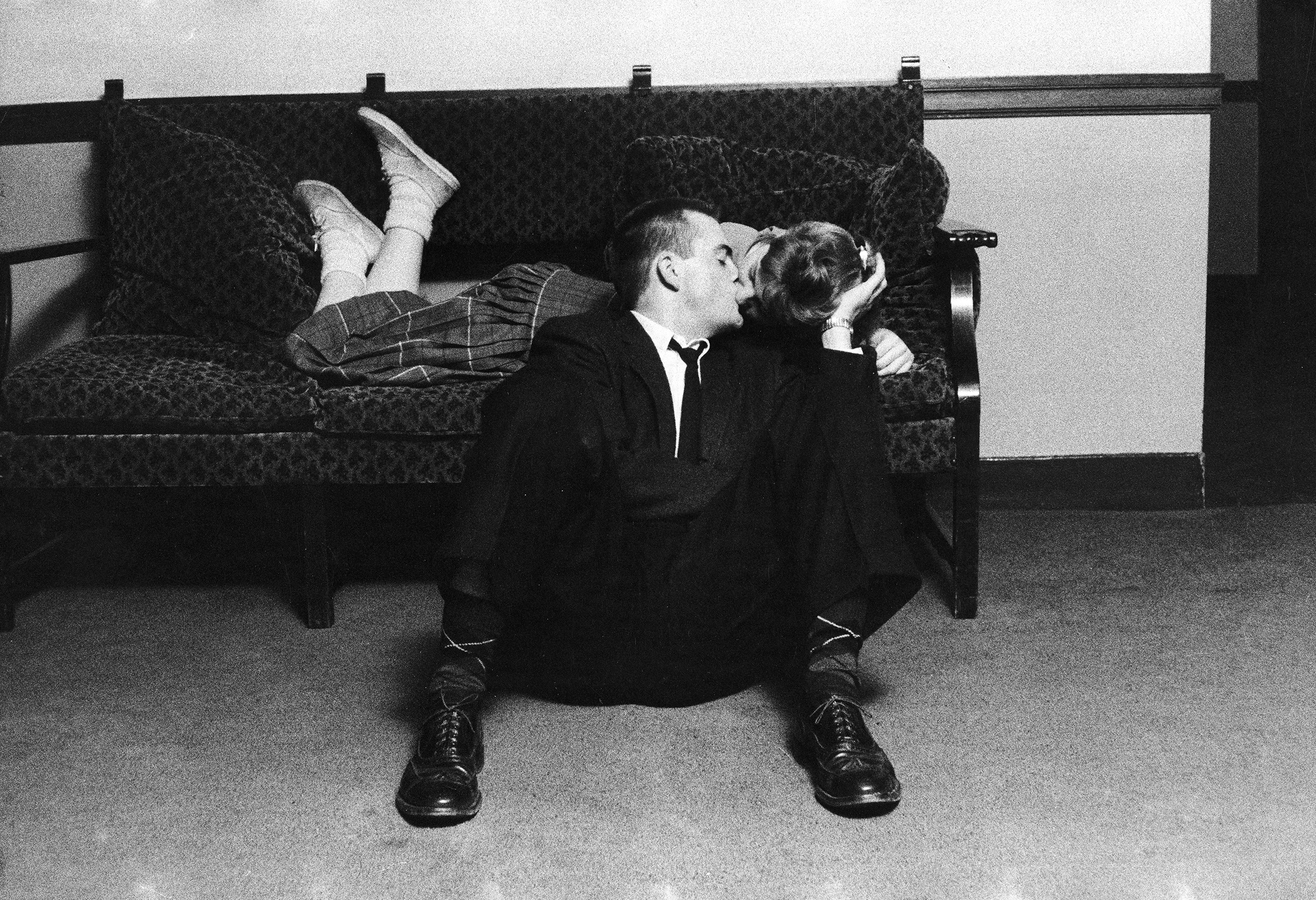A University of Michigan student couple engaged in an impromptu kiss in the Union Building on campus. 1957. This was forbidden conduct because rules required couples to have both feet on the floor.