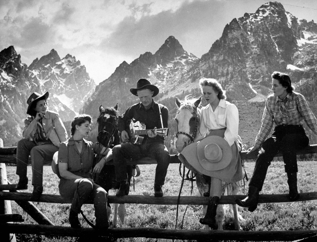 Friends sat on a fence and sang along to the guitar, 1941.