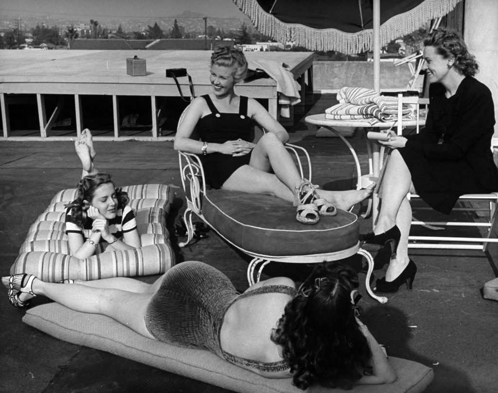 Joan Caulfield (C) and friends enjoying the sun while a reporter interviews her, 1946.