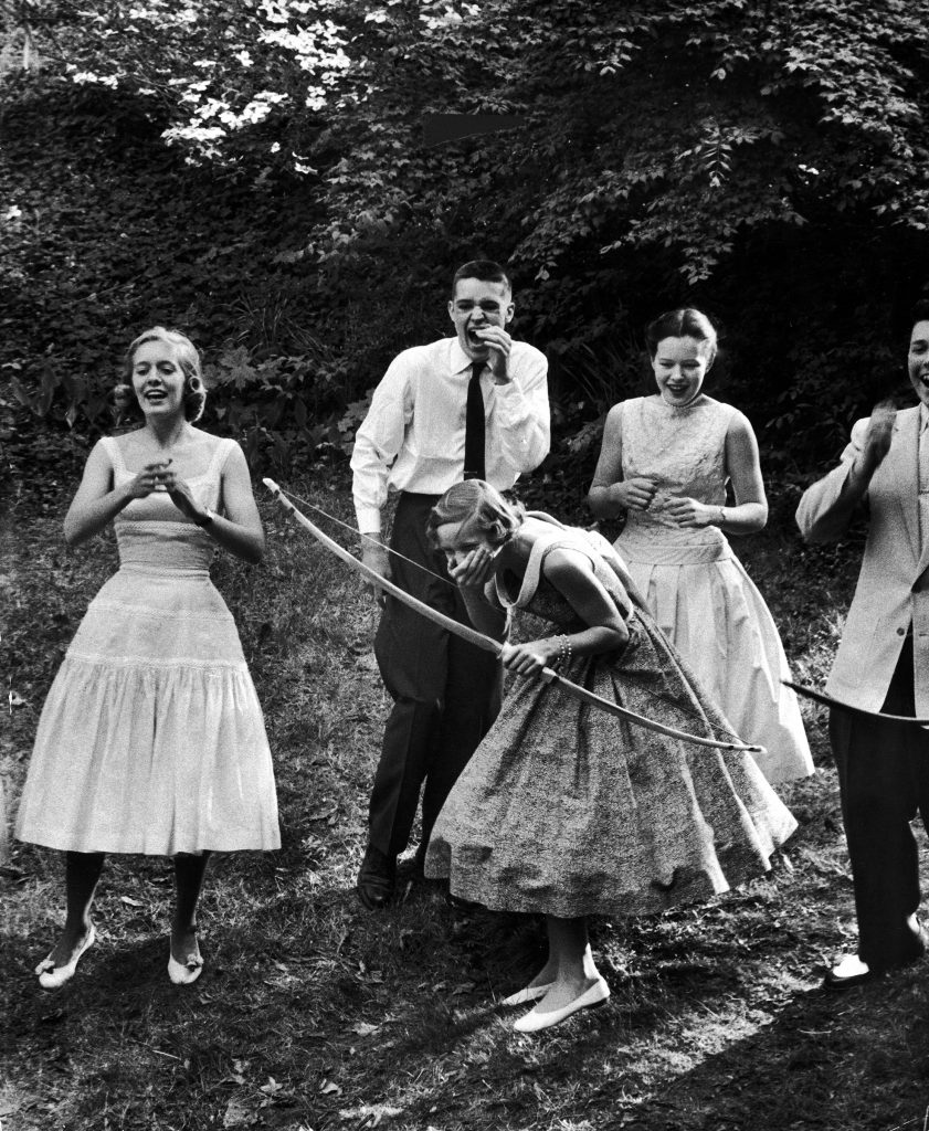 Archery providing entertainment for a group of friends at a teenage party, 1956.