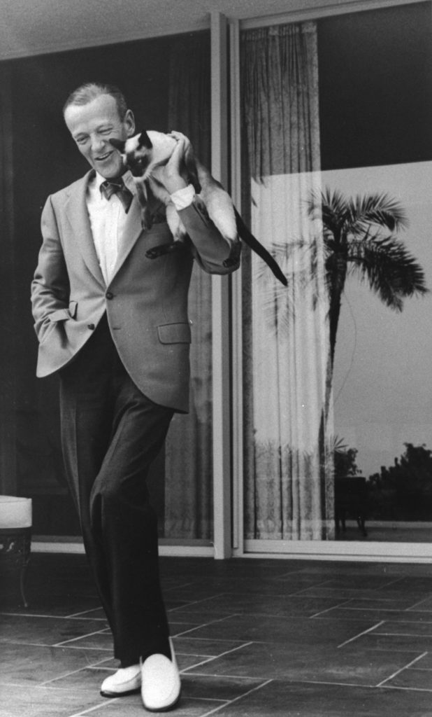 Fred Astaire dancing with his Siamese cat on his shoulder, 1962.