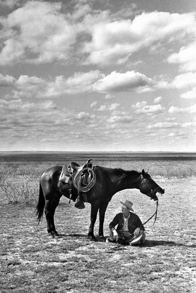 Foreman of the JA Ranch Clarence Hailey Long sitting in shade of his horse on prairie, 1949.
